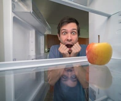 Hungry man is looking for food in fridge and is shocked. Only apple is inside empty fridge.